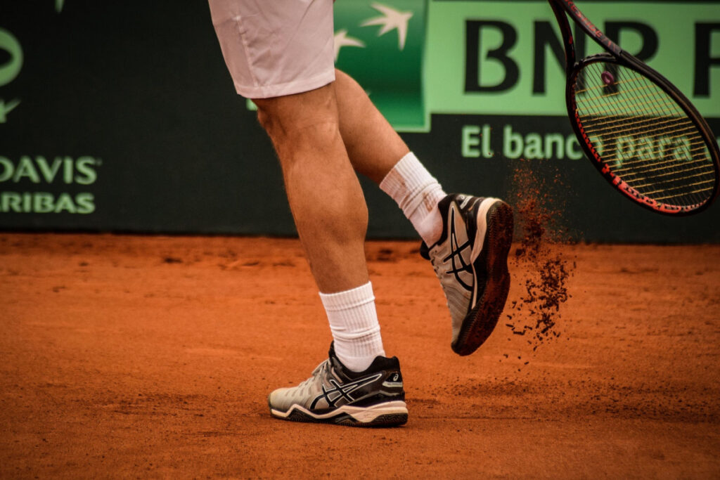 Tennis player getting clay out of his shoe