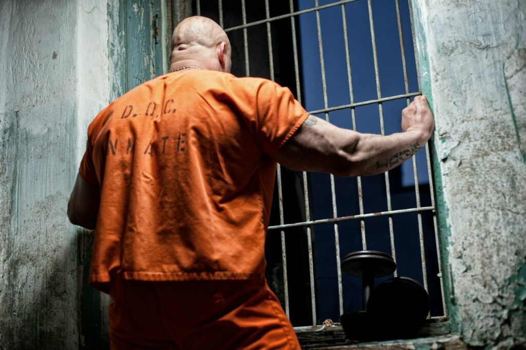 Prisoner looking out of a window. The prisoner's dilemma is a good example of the importance of sportsmanship